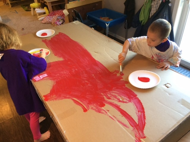 preschool boy painting red on a large piece of cardboard for fire safety activity