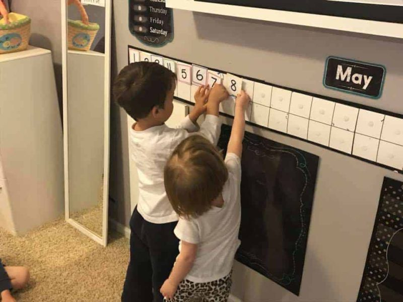 young boy and girl adding number cards to a calendar wall
