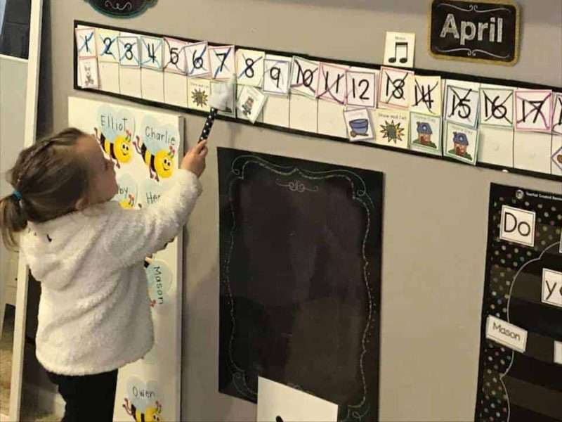 preschool girl wearing white sweatshirt pointing to numbers on the calendar with a wand