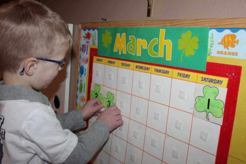 boy with glasses putting numbers on a march calendar
