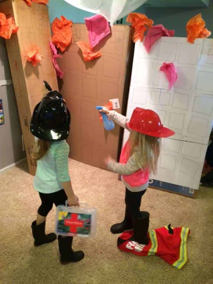 two preschool girls dressed as fire fighters pretending to put out fire for fire safety dramatic play