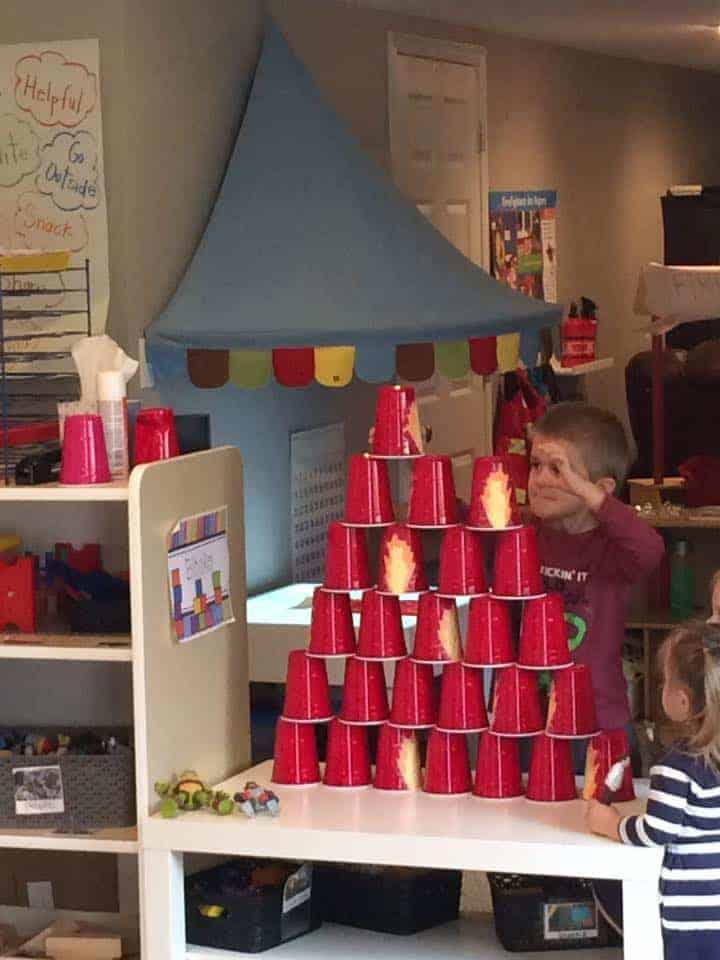 young boy stacking red fire cups to make a tower for fire safety science activity