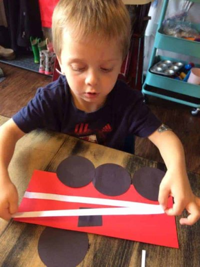 preschool boy creating a firetruck out of paper and glue