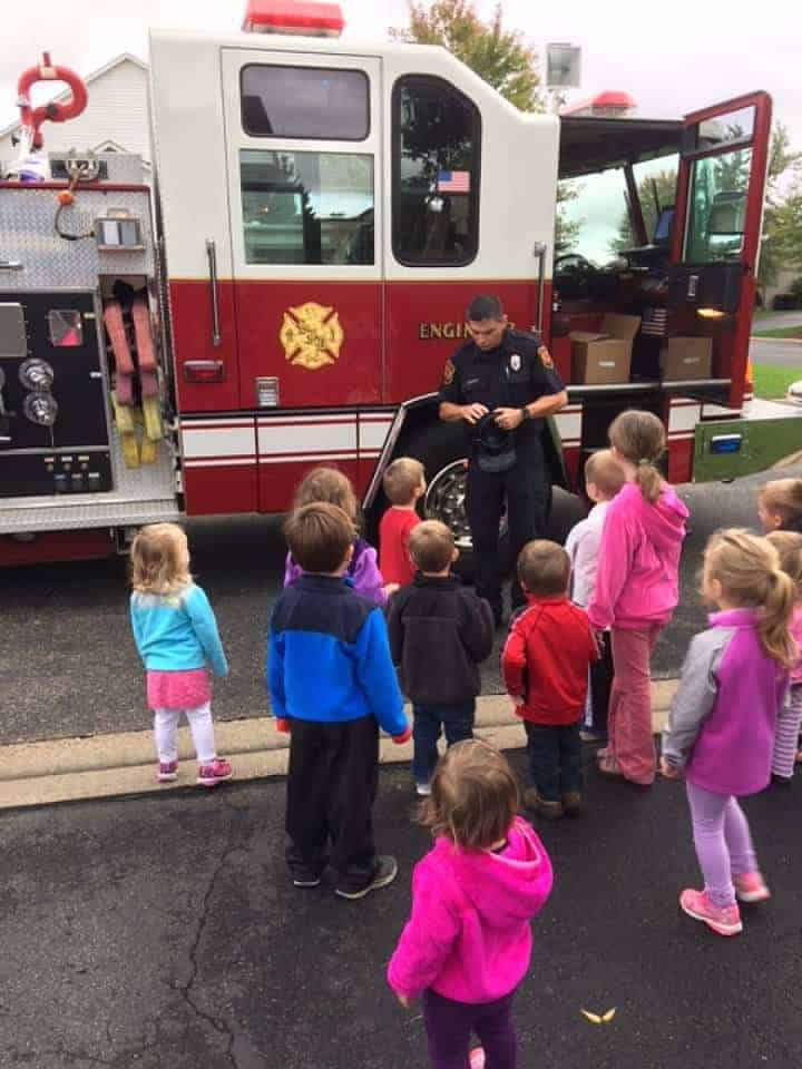 fire fighter talking to group of young kids in front of fire truck
