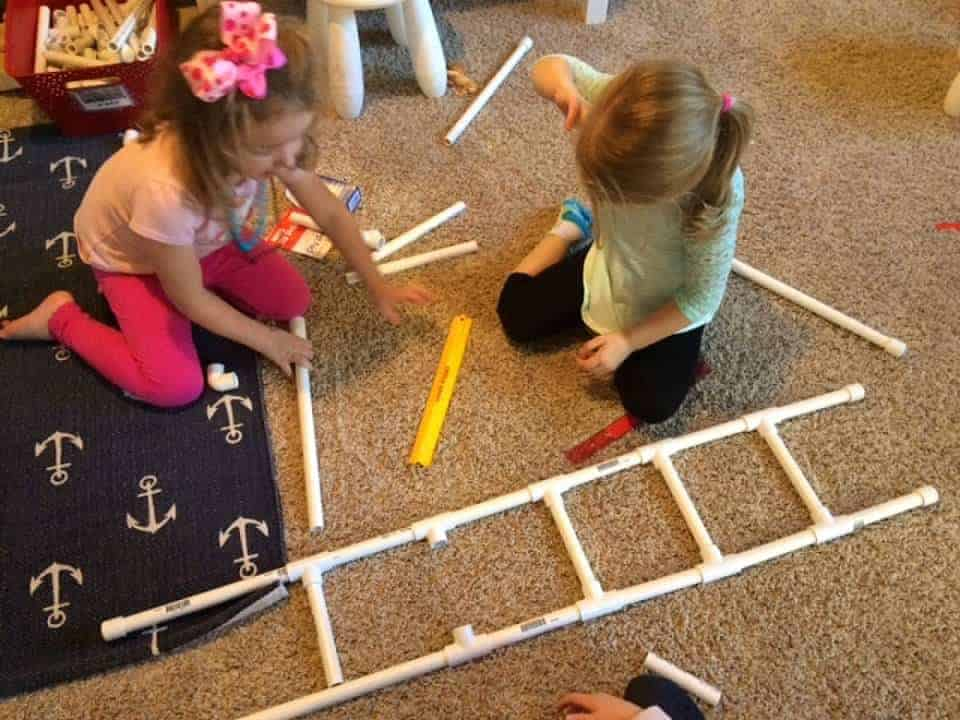 two girls building a ladder with pvc pipes for fire safety week