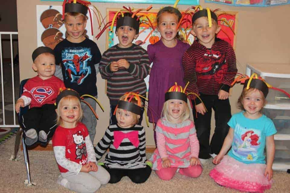 group of preschoolers smiling with paper fire hats for fire safety week activity idea