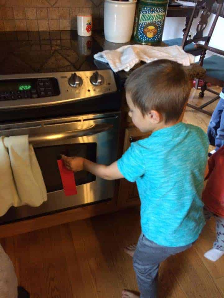 boy placing red paper strip on oven door fire safety activities