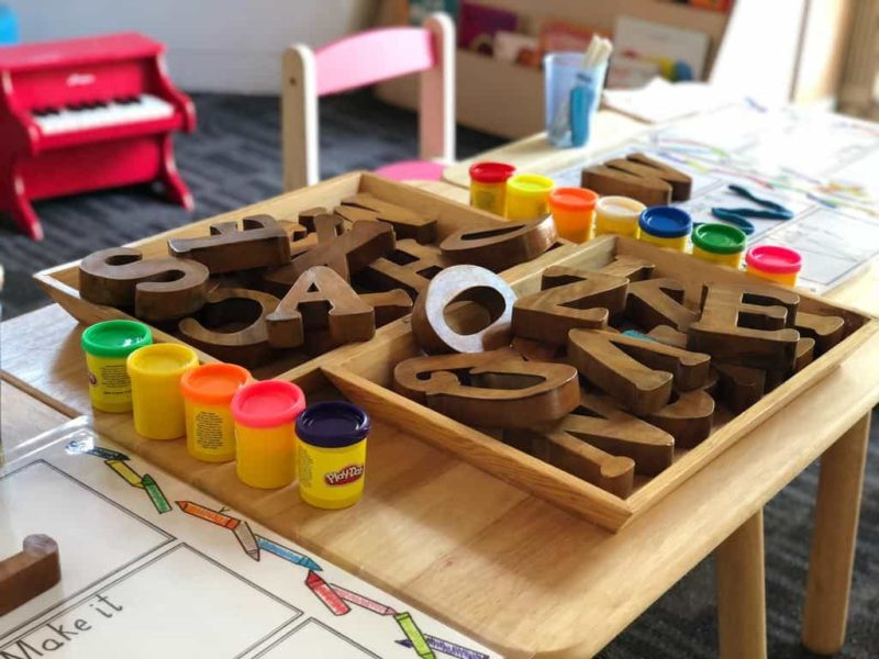 preschool classroom pile of wooden letters and playdoh on a table