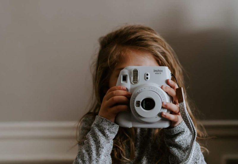 young girl holding a camera up to her face marketing in child care