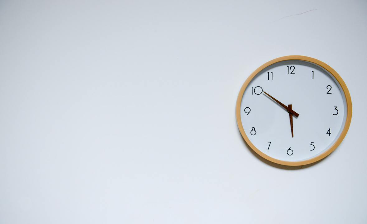 clock hanging on a white wall showing daycare pick up time