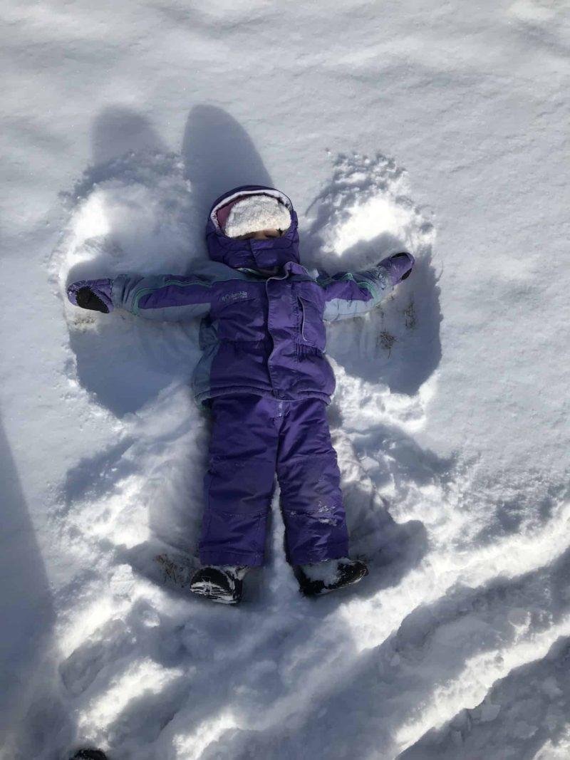 little girl in purple winter gear making snow angel