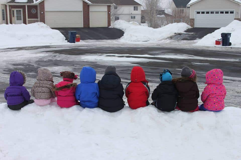 row of young kids sitting on snowbank in snow gear