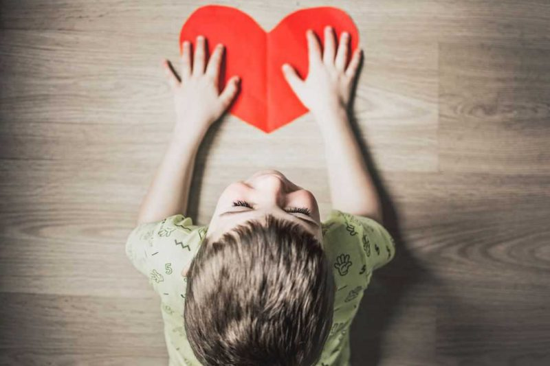 boy holding paper heart on table