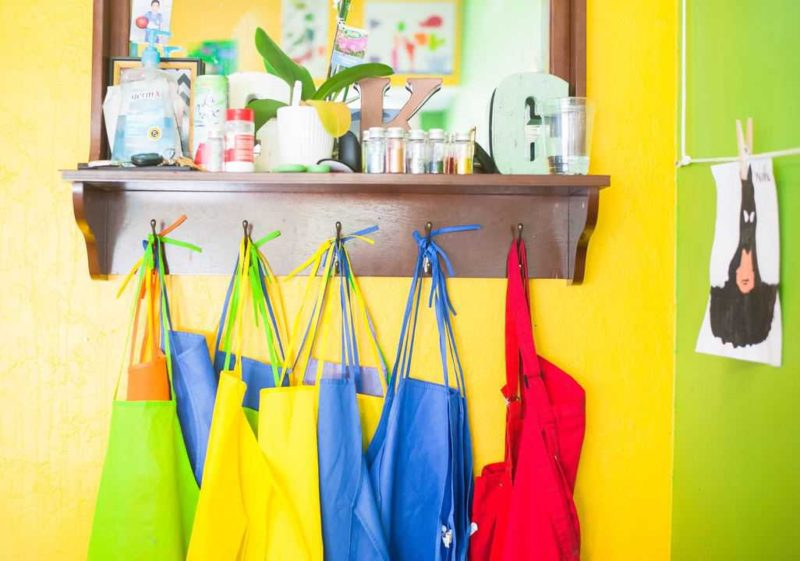 row of colorful aprons hanging in brightly colored classroom
