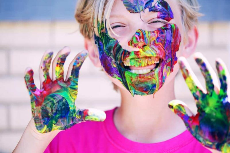 child with paint on face and hands