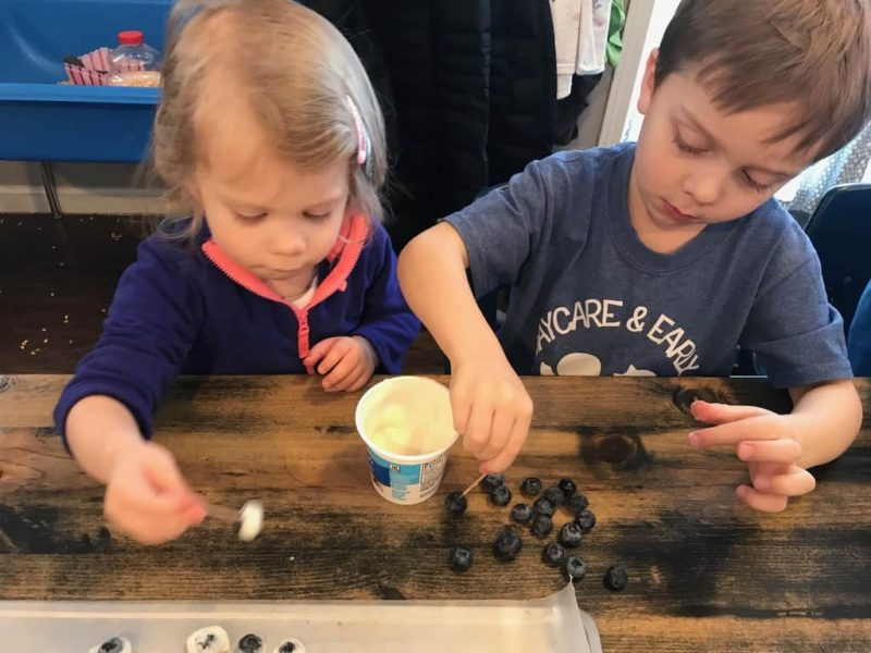 boy and girl dipping blueberries in yogurt