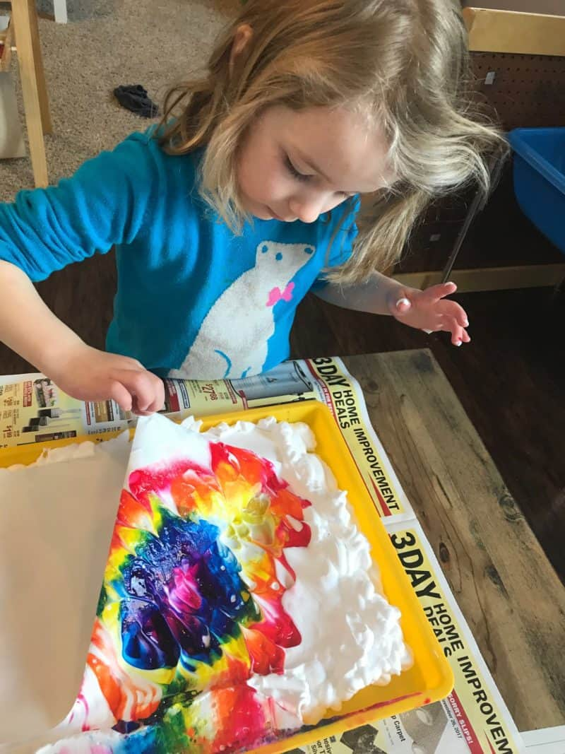 young girl painting with shaving cream