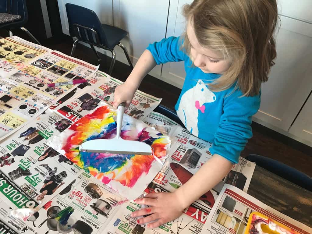 young girl using a squeegee on paint and paper