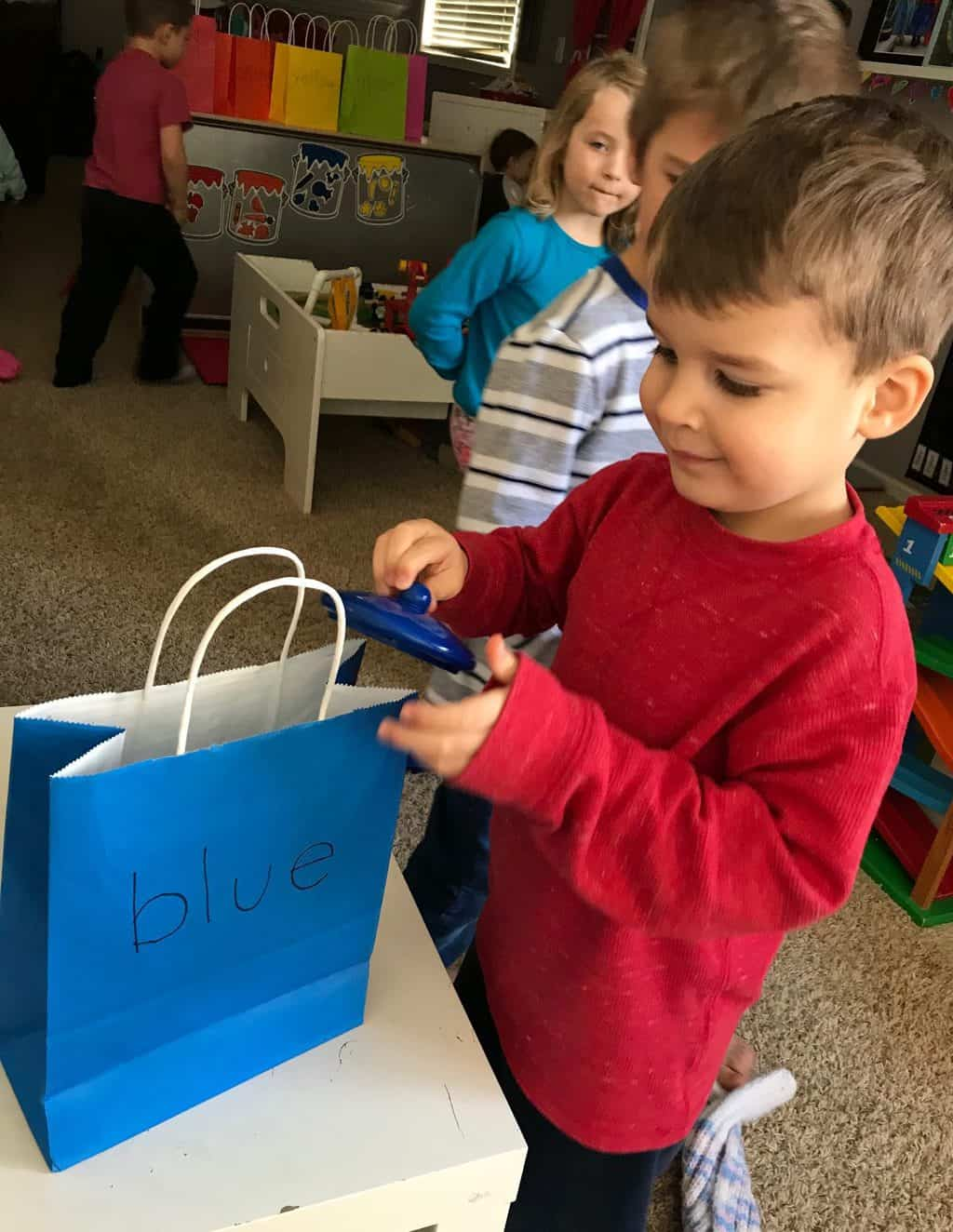 young boy with blue gift bag