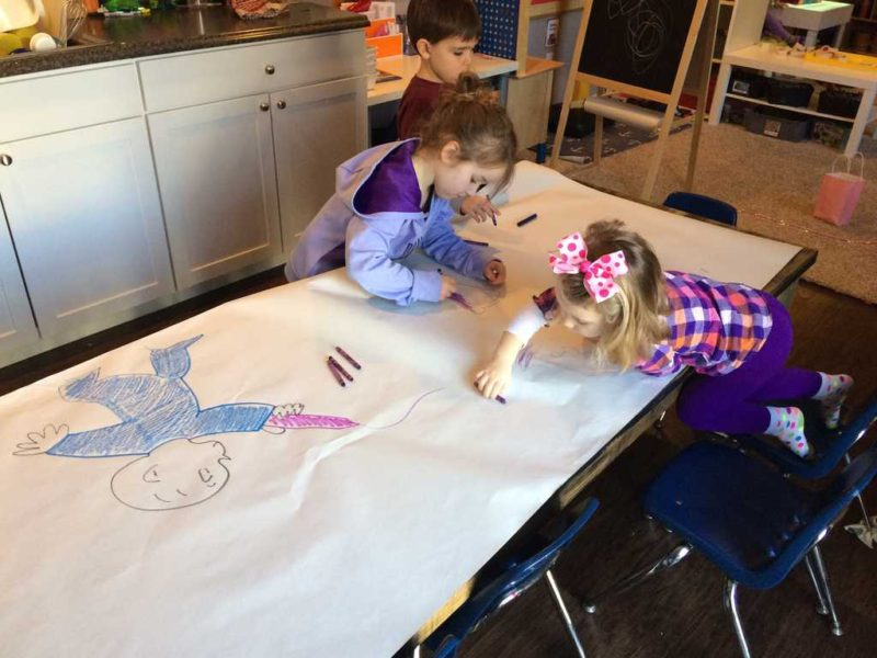 kids coloring on a large sheet of paper at the table