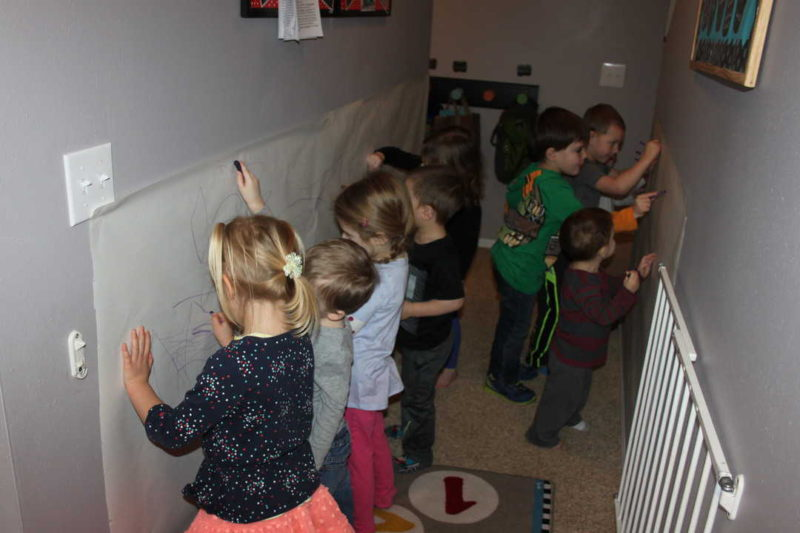 kids coloring with purple crayon on the wall