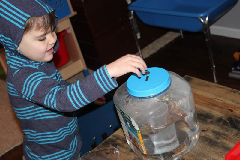 young boy dropping a coin into jar of water for a presidents' day activity