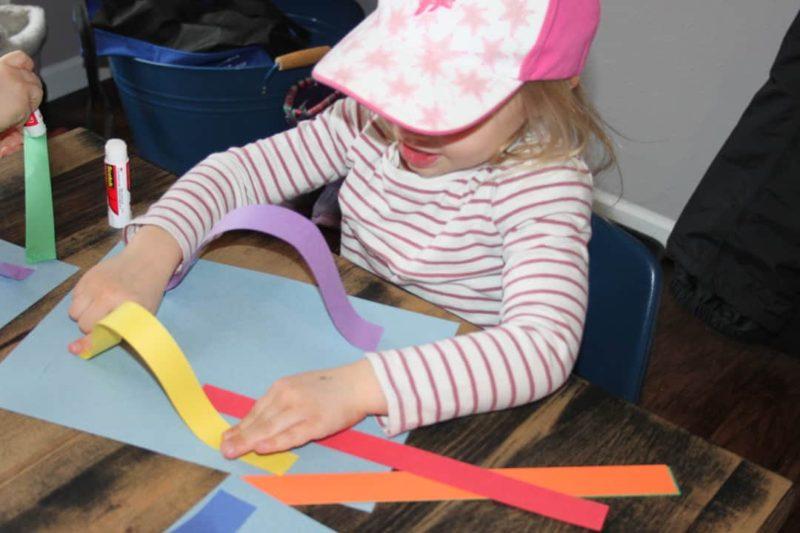 young girl gluing colorful strips to paper