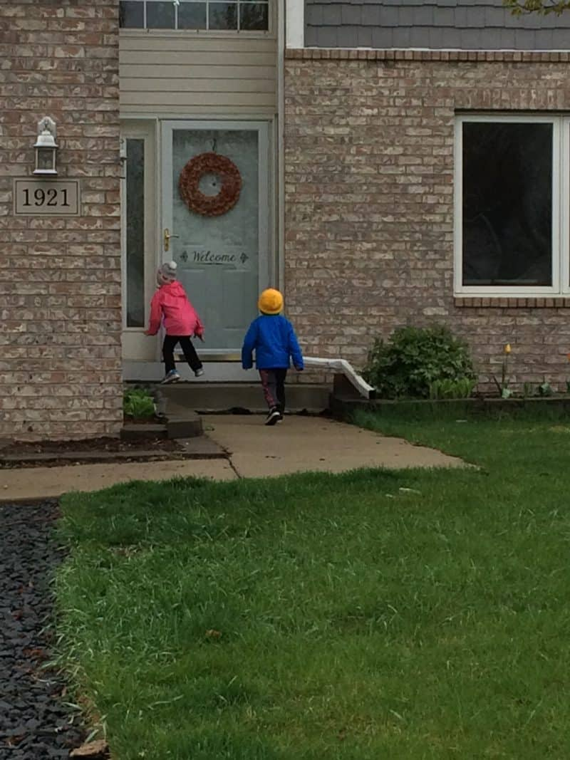 2 young children ringing doorbell on may day with basket