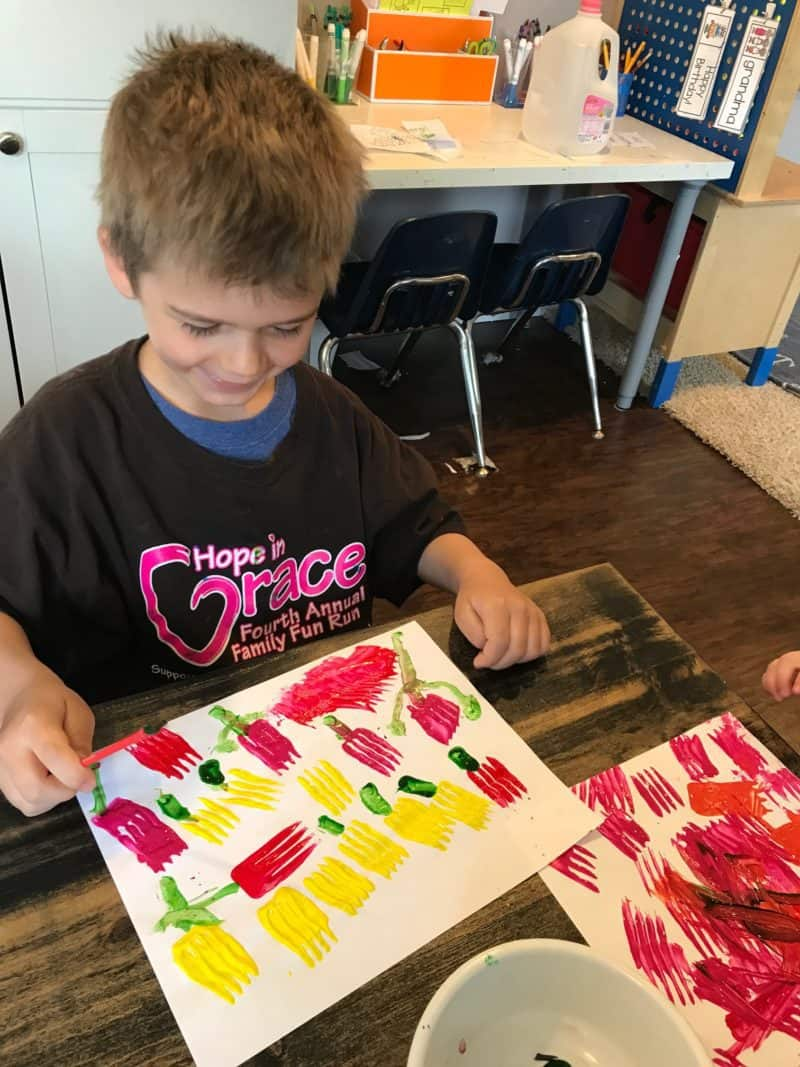 young boy smiling and painting tulips