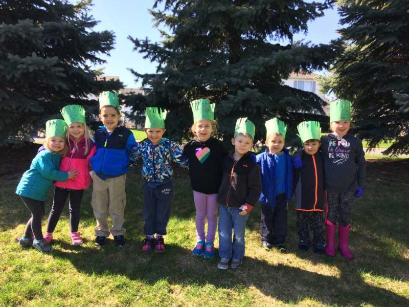 group of preschoolers standing in line wearing paper earth day crowns