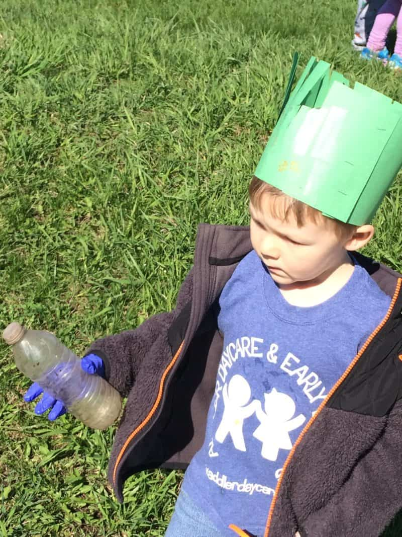 young boy picking up litter during earth day activities