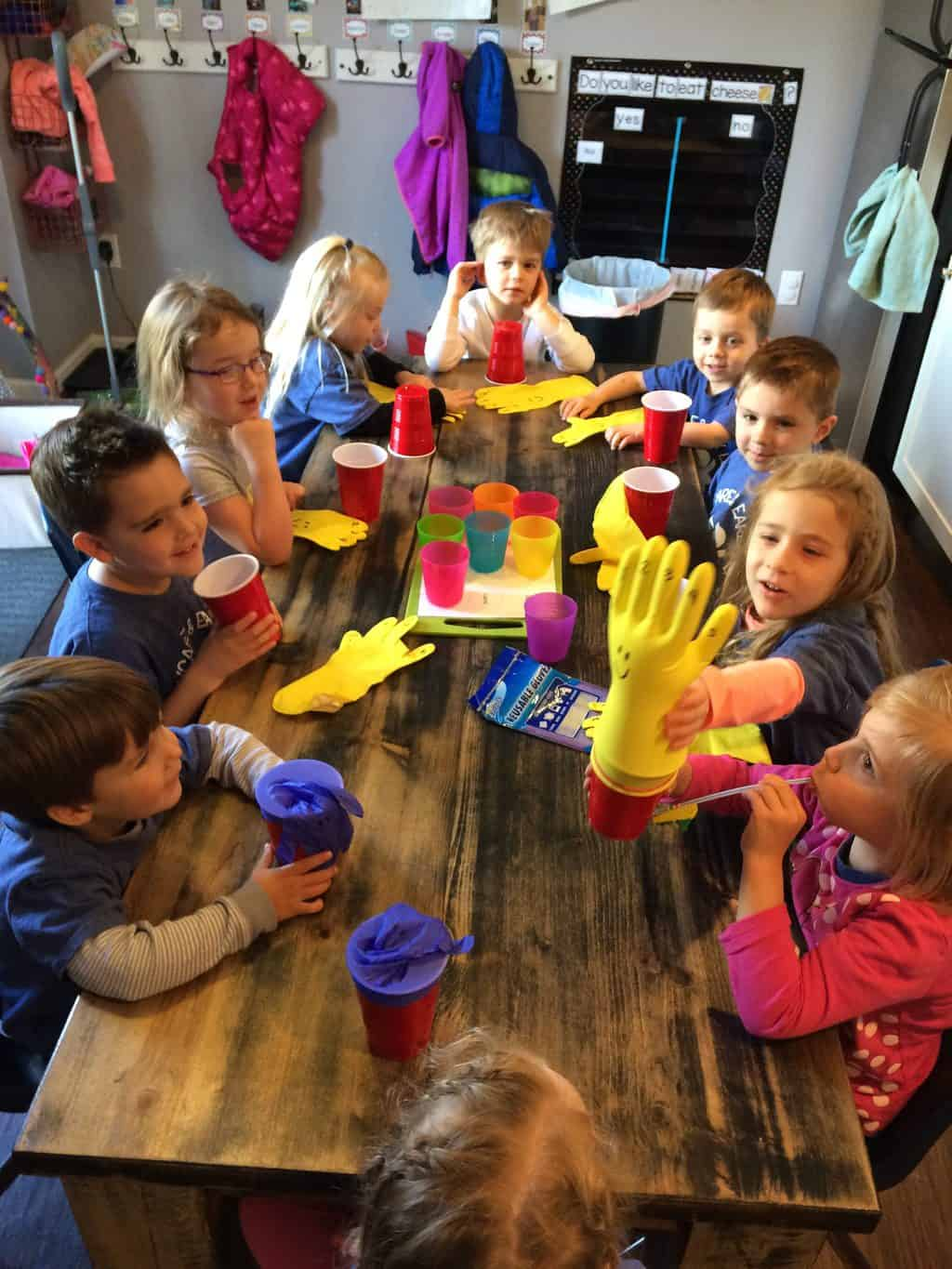 science activities for preschoolers with group of young kids making glove and cup project