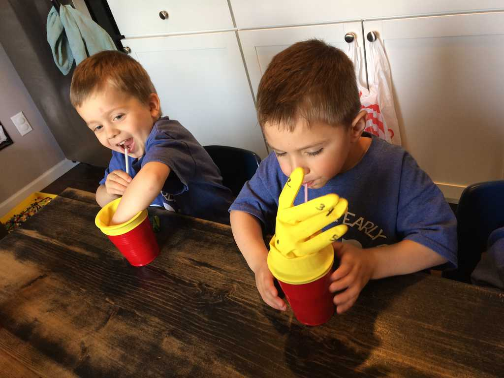 science activity for preschoolers two young boys blowing into  straw and cup