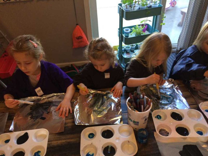 young kids painting on foil during sensory art activity