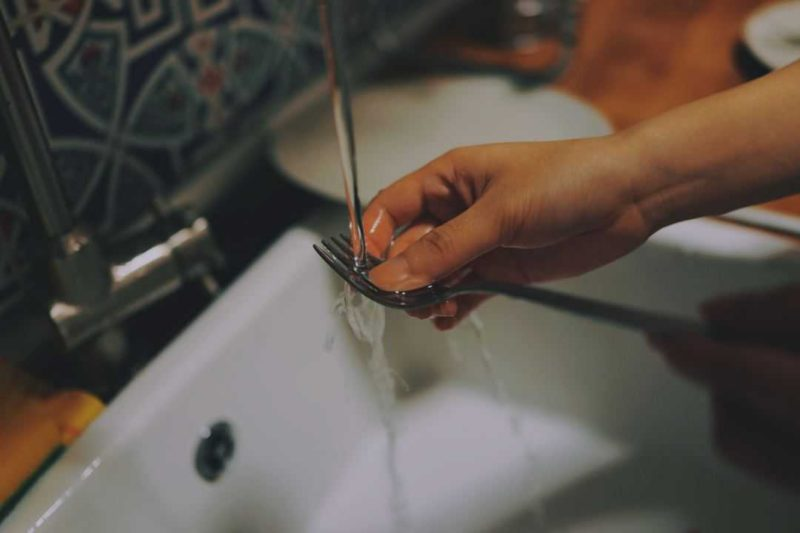 person washing a fork in the sink