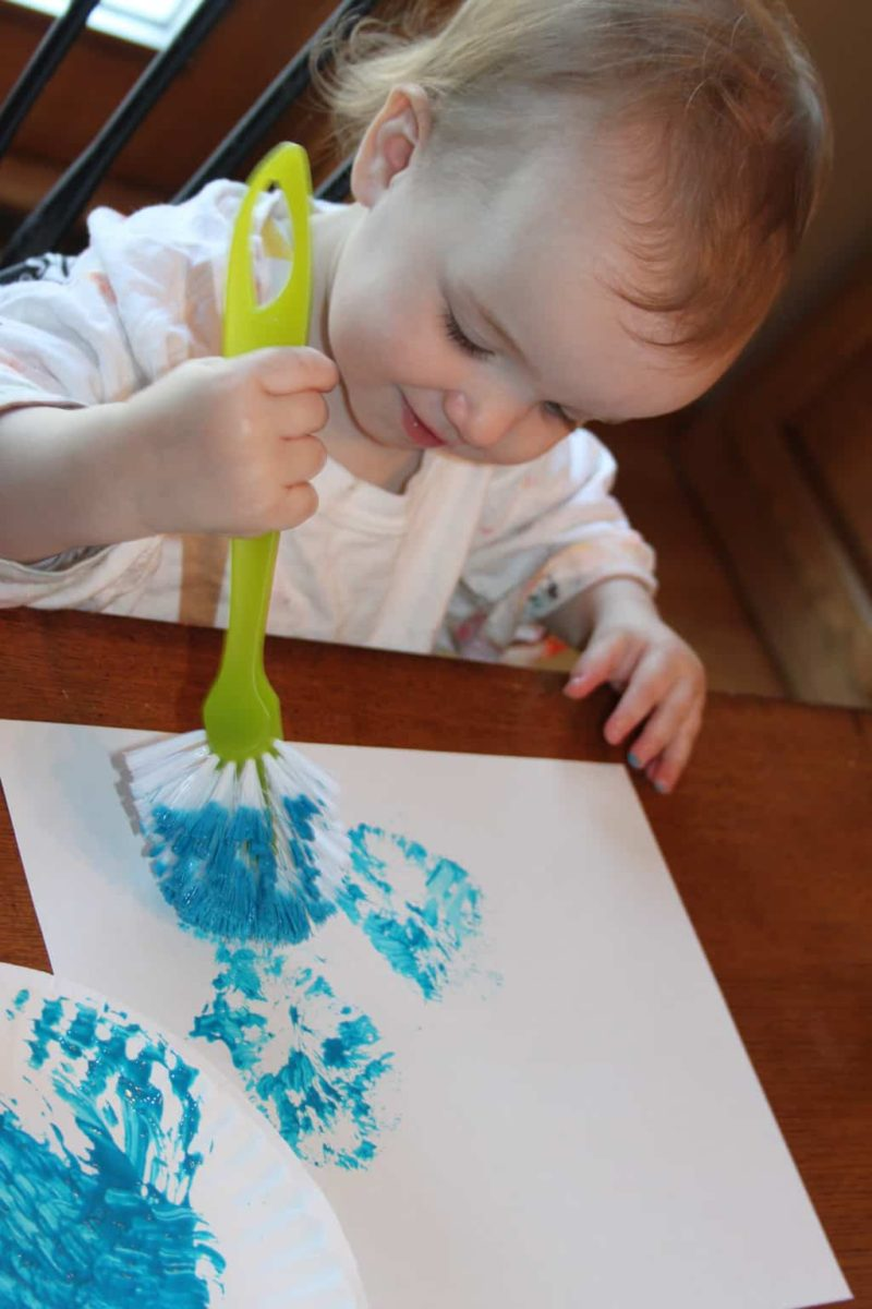 toddler girl painting with a blue scrub brush