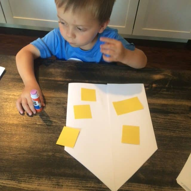 preschool boy gluing yellow squares on paper house