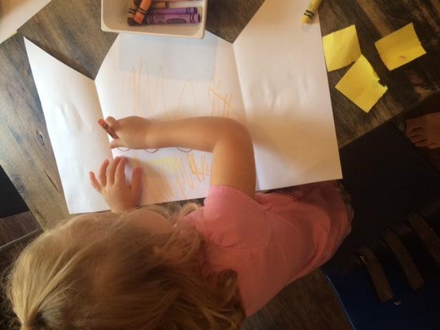 preschool child gluing squares on paper