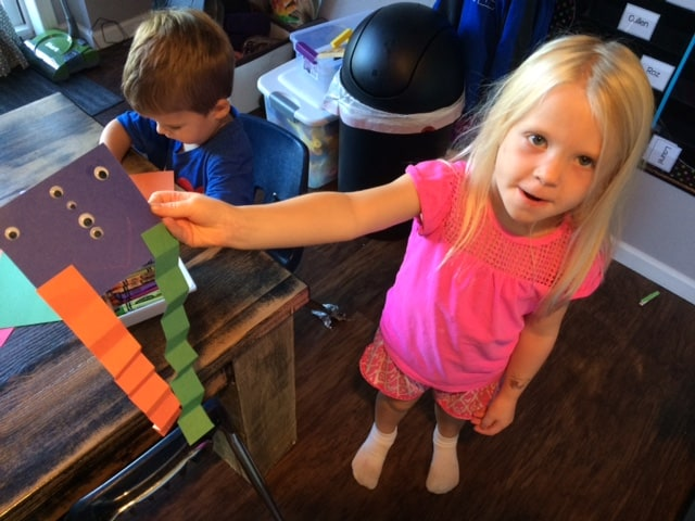 young girl holding up a finished construction paper project in preschool