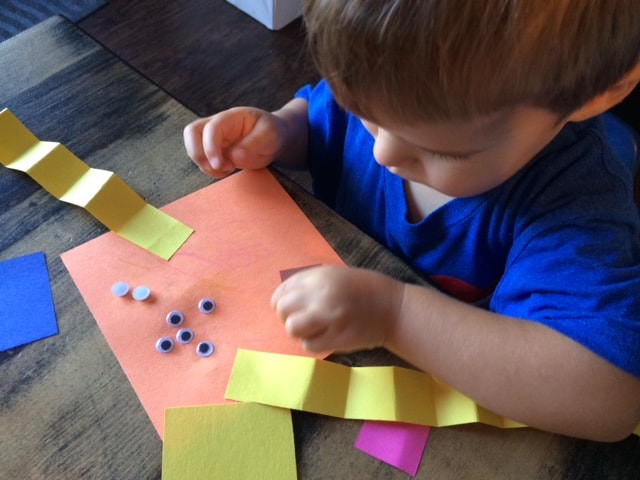 young boy gluing googly eyes to construction paper