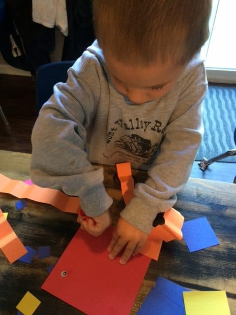 young boy doing a gluing activity