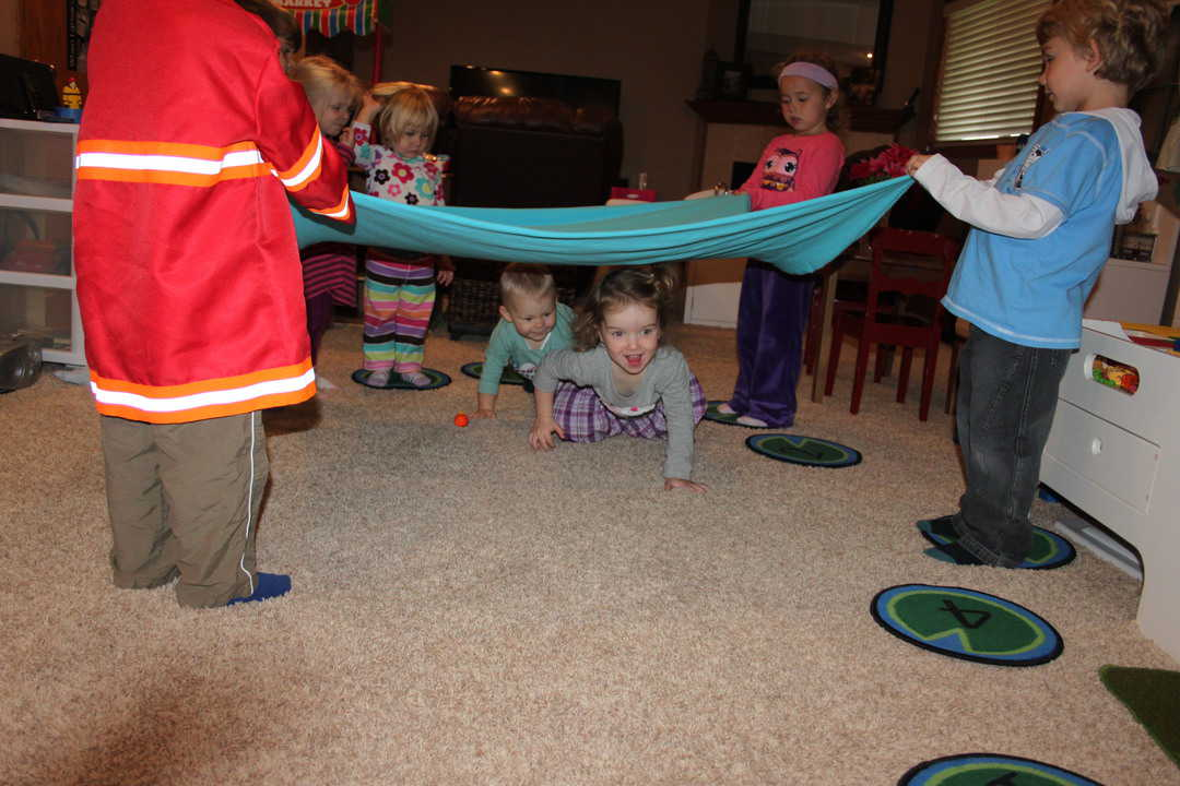 young children holding a sheet for other kids to crawl under