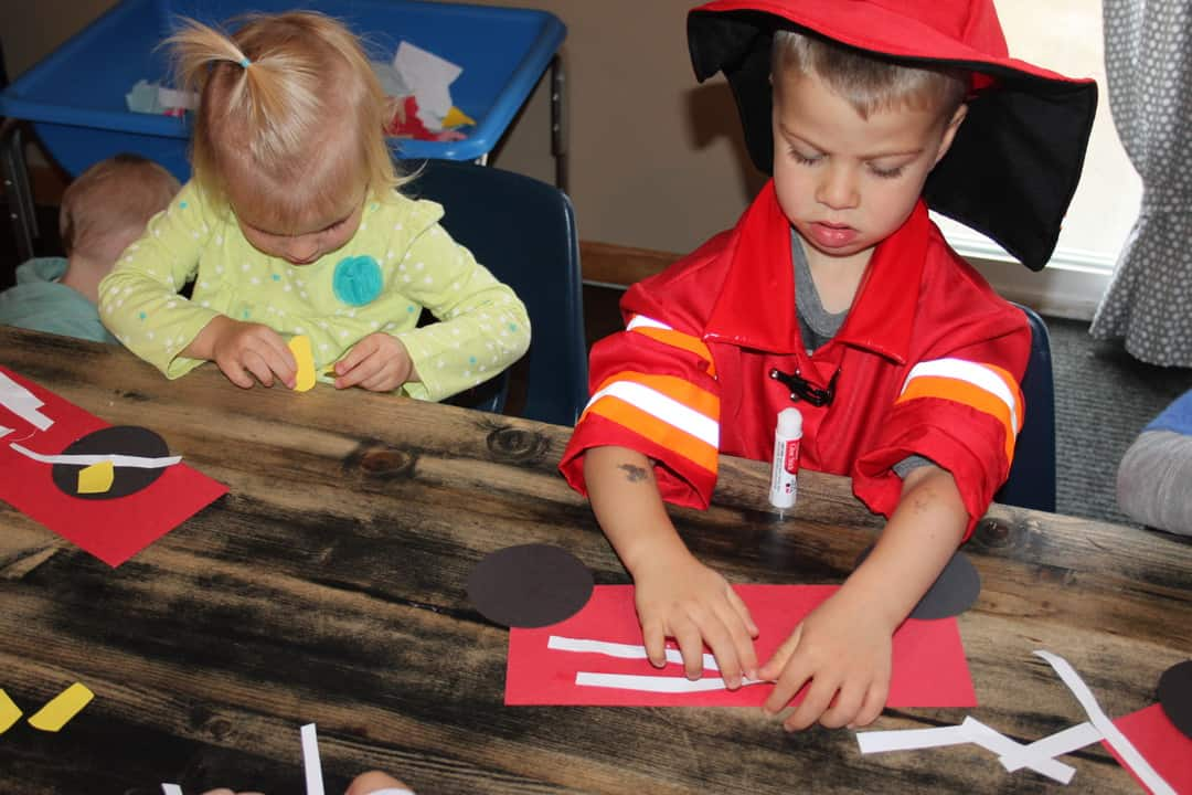 young in fire fighter costume making a paper fire truck for fire safety craft for preschoolers