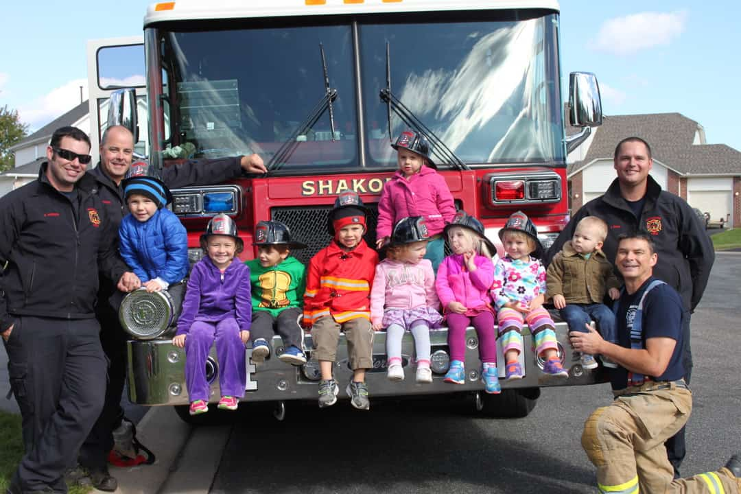 group of young kids sitting on fire truck with firefighters