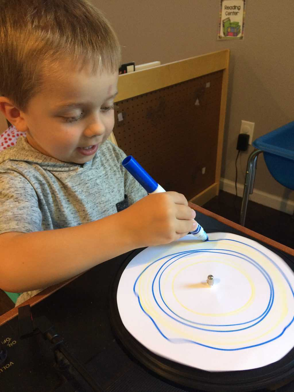 young boy working with record player and marker to make art