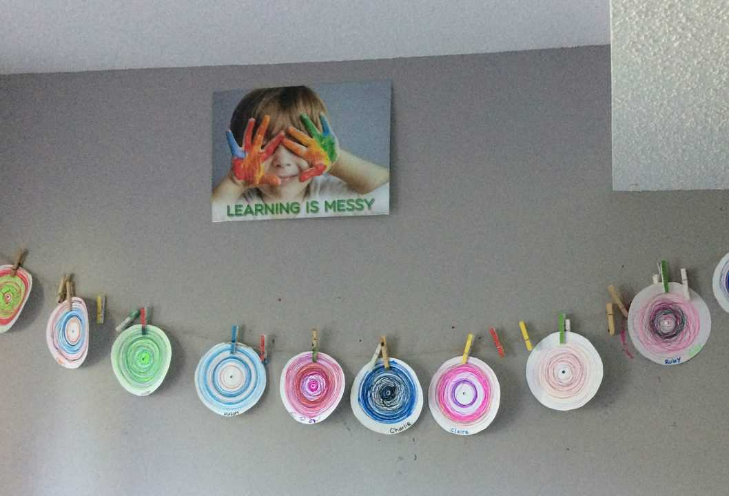 row of colorful circle drawings hanging on a wall