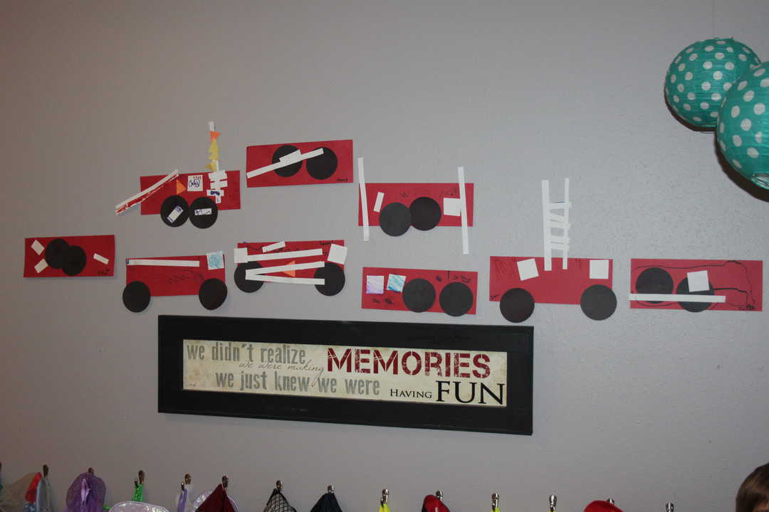 row of homemade paper fire trucks on the wall display for fire safety week