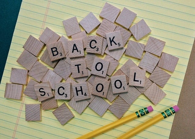 scrabble tiles in a pile that spell out back to school