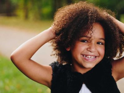 young girl with curly brown hair and hands on her head smiling