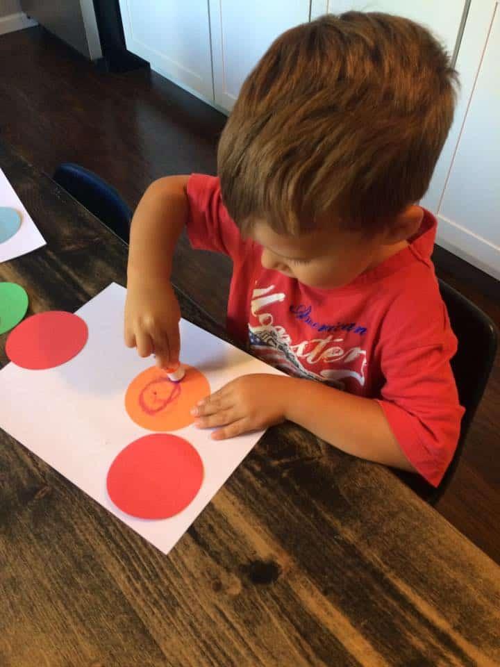 preschool boy learning how to use a glue stick